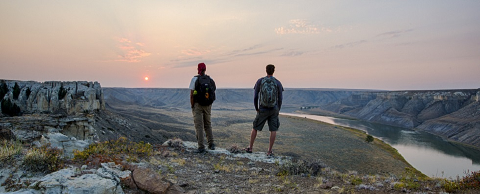 Two Men looking out over beautiful peach and pink sunset on top of a vast and rocky canyon